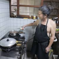 The aproned chef: Masashi Miyagi adds a dash of liquor to a soup. | STEPHEN MANSFIELD