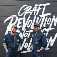 Denim-clad pioneers: Tokyo Aleworks head brewer Bob Stockwell (right) and production adviser Randy Carncross pose outside the premises. | CLAIRE WILLIAMSON
