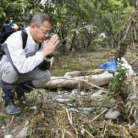 Last respects: A man prays on Oct. 18 at a place where a homeless man whose body was discovered in the Tama River in Hino, Tokyo, used to live before Typhoon Hagibis struck the capital four days earlier. | KYODO
