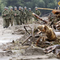 At the mercy of nature: Ground Self-Defense Force members inspect the extent of damage caused by Typhoon Hagibis in Marumori, Miyagi Prefecture, on Oct. 19. | KYODO