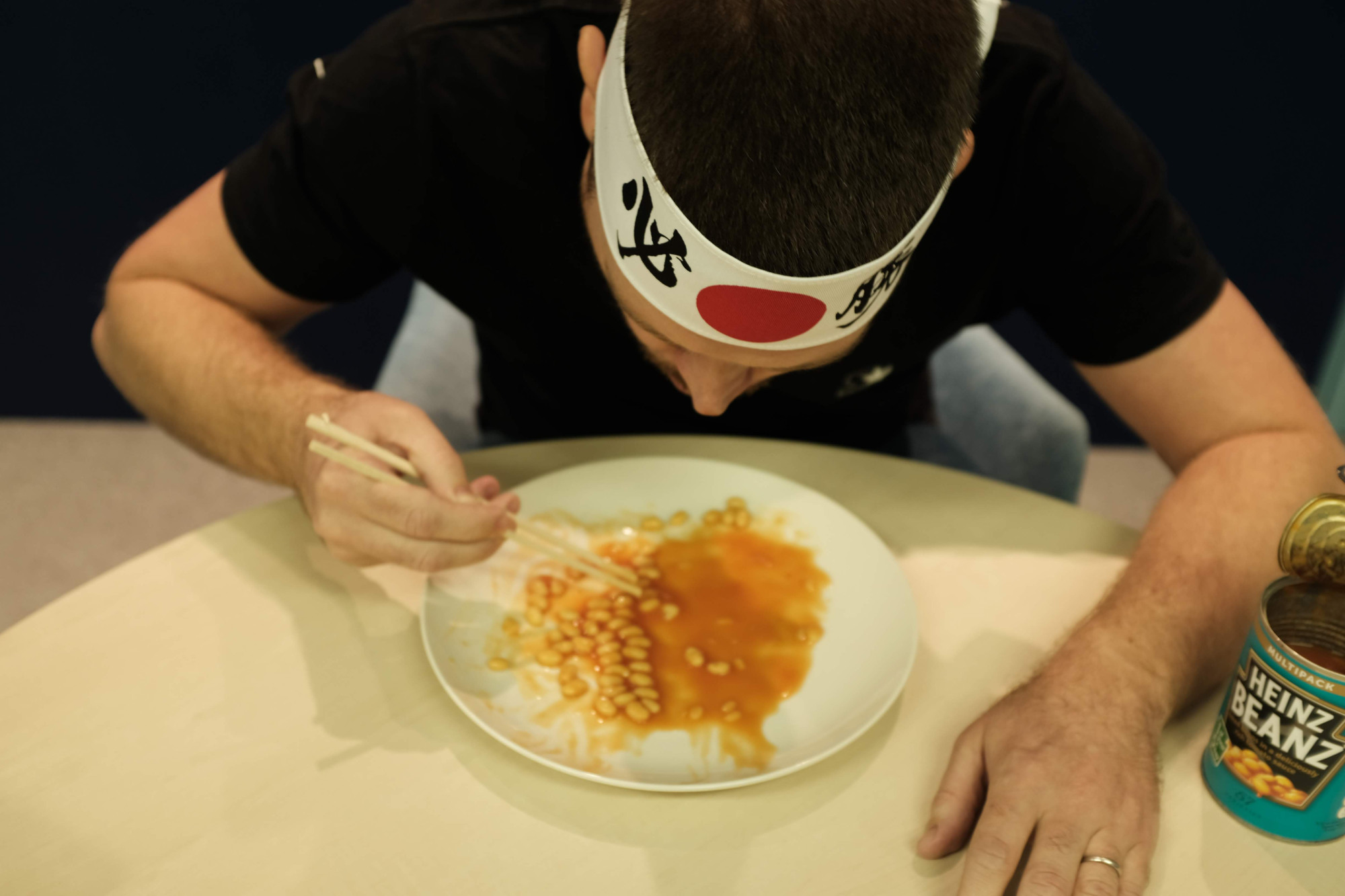 The Japan Times' Andrew McKirdy attempts to break the world record for most baked beans eaten with chopsticks in one minute at the Guinness World Records Japan office in November. | CHISATO TANAKA