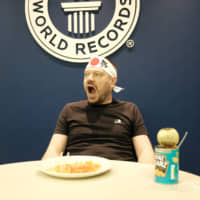 The Japan Times' Andrew McKirdy shows an adjudicator from Guinness World Records that his mouth is empty in an attempt to break the world record for most baked beans eaten with chopsticks in one minute in November. | CHISATO TANAKA
