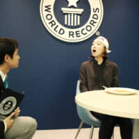 An adjudicator from Guinness World Records checks that Japan Times reporter Chisato Tanaka has an empty mouth in her attempt to break the world record for most baked beans eaten with chopsticks in one minute in November. | ANDREW MCKIRDY