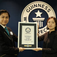The Japan Times' Chisato Tanaka receives a certificate from Guinness World Records after successfully breaking the world record for most baked beans eaten with chopsticks in one minute in November. | ANDREW MCKIRDY