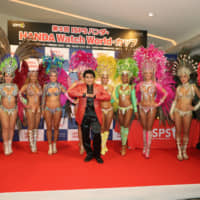 International Sports Promotion Society Chairman Haruhisa Handa (center) and feather-clad Brazilian samba dancers at a dinner following the first day of the ISPS Handa Watch World Cup at Taiheiyo Club Gotemba West in Shizuoka Prefecture on Nov. 4 | ISPS
