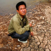 A Thai farmer sits beside a drought-stricken irrigation canal fed by the Mekong River in 2010. | BLOOMBERG