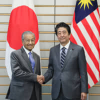 Malaysian Prime Minister Tun Dr. Mahathir Mohamad and Japanese Prime Minister Shinzo Abe shake hands during their meeting in Tokyo on May 31. Mahathir has adopted the Look East Policy modeled after Japan's economic growth since his first term as prime minister between 1981 and 2003. | CABINET PUBLIC RELATIONS OFFICE