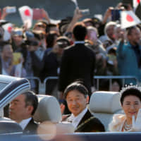 Emperor Naruhito and Empress Masako wave to well-wishers watching the Nov. 10 enthronement parade. | REUTERS