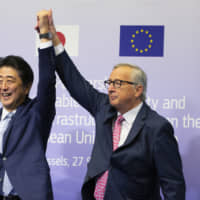 Prime Minister Shinzo Abe and European Commission President Jean-Claude Juncker demonstrate their solidarity following the signing of a partnership agreement between Japan and the European Union in Brussels on Sept. 27. | AP