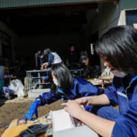 Student volunteers in Date, Fukushima Prefecture, clear debris Oct. 16 from an elderly person's home in the aftermath of Typhoon Hagibis. | REUTERS