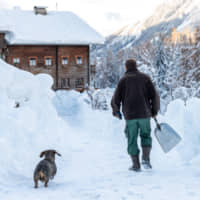 A man clears snow around a house on Monday after heavy snowfalls in Kals am Grossglockner, Austria. | AFP-JIJI