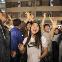 Pro-democracy supporters celebrate after pro-Beijing politician Junius Ho lost his election in Hong Kong on Monday. Hong Kong's pro-democracy opposition won a stunning landslide victory in the Sunday election, dealing Beijing a massive defeat. | AP