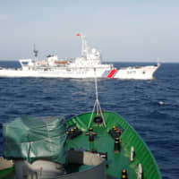 A China Coast Guard ship passes in front of a Vietnam Marine Guard vessel in the South China Sea about 210 km of the coast of Vietnam in May 2014. A festering territorial dispute in the South China Sea has raised tensions between the two neighbors. | REUTERS