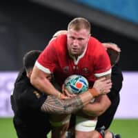 Wales' Ross Moriarty (C) is tackled by New Zealand players on Friday night. | AFP-JIJI