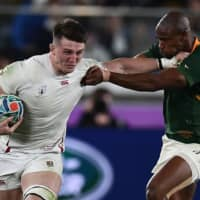 South Africa's Makazole Mapimpi (right) tackles England's Tom Curry in the Rugby World Cup final on Saturday at International Stadium Yokohama.   AFP-JIJI