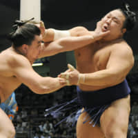 Chiyotaikai (right) grapples with Ama, who would later become Harumafuji, during the 2008 Nagoya Grand Sumo Tournament. | KYODO
