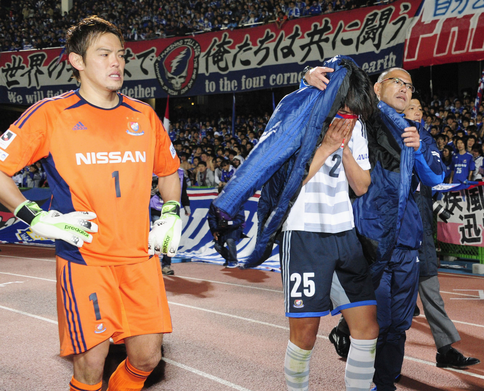 Yokohama F. Marinos captain Shunsuke Nakamura (center) is comforted by club staff after the team's loss to rival Kawasaki Frontale on Dec. 7, 2013, the final day of that year's J. League season, at Todoroki Stadium. | KYODO