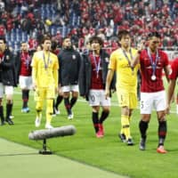 Urawa Reds players walk off the field with their second-place medals draped around their necks. | KYODO