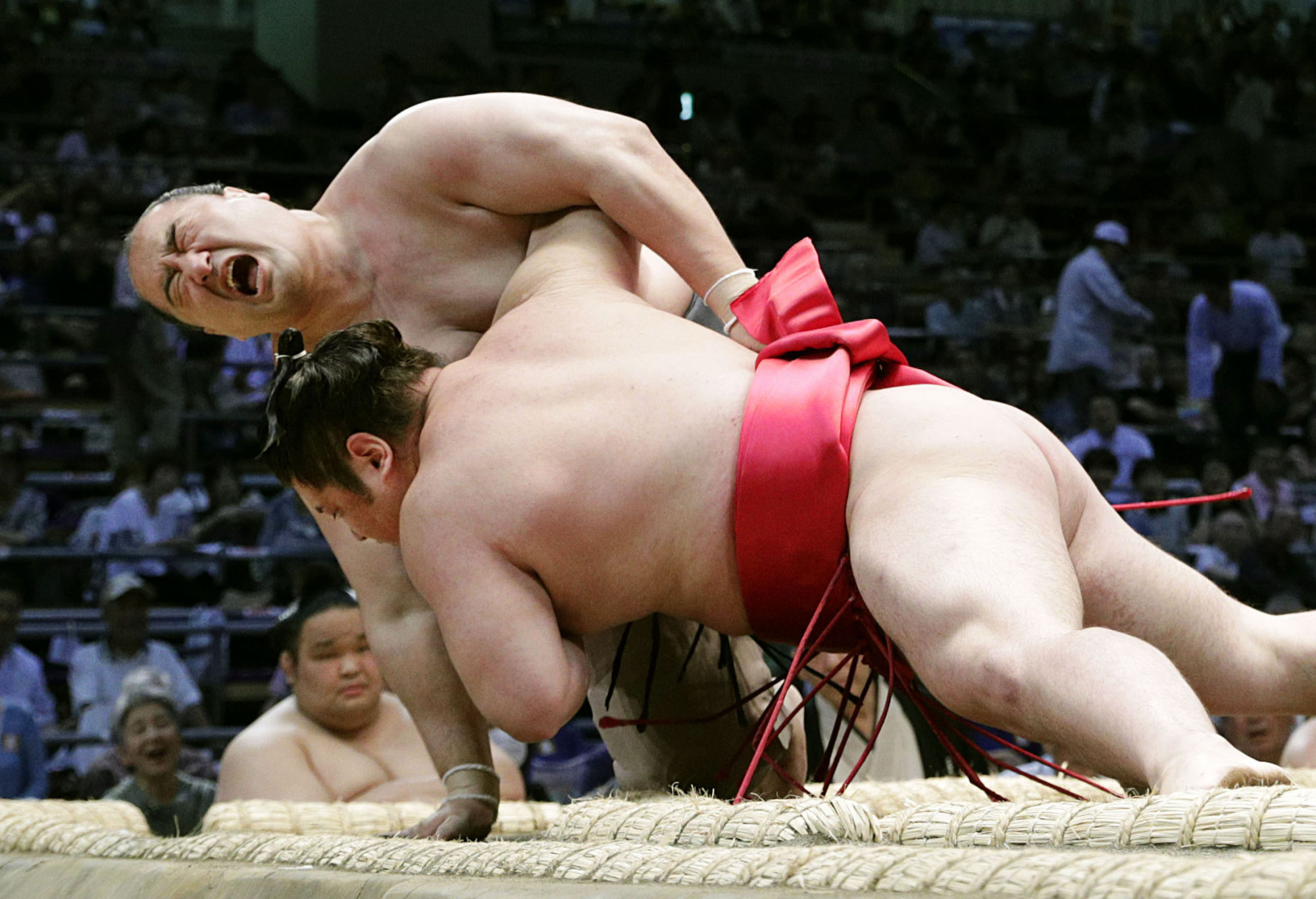 Former sekiwake Aminishiki suffers a right knee injury during a juryo bout against Ryuko on the second day of the Nagoya Basho on July 8. Then-40-year-old Aminishiki withdrew from the tourney and eventually retired because he was to face the demotion from juryo and lose the sekitori status (wrestlers in makuuchi and juryo divisions) that he had kept for 19 years. | KYODO