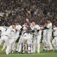 Samurai Japan players celebrate on the mound after beating South Korea to win the Premier12 title on Sunday at Tokyo Dome. | KYODO