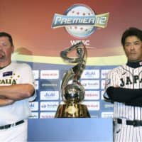 Japan manager Atsunori Inaba (right) and Australia manager David Nilsson pose with the Premier12 trophy on Sunday. | KYODO