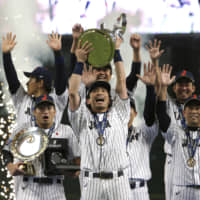 Samurai Japan infielder Nobuhiro Matsuda lifts the Premier12 trophy as his teammates celebrate after their 5-3 win over South Korea in the final on Sunday at Tokyo Dome. | AP