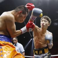 Naoya Inoue (right) throws a punch at Nonito Donaire in the second round on Thursday night. | KYODO
