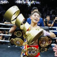 Naoya Inoue holds the Muhammad Ali Trophy after his triumph on Thursday night. | KYODO