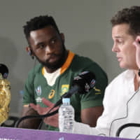 South Africa's Siya Kolisi looks at coach Rassie Erasmus at a news conference after the team defeated England in the Rugby World Cup final at International Yokohama Stadium in the city on Saturday. | AP