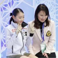 Rika Kihira (left) smiles with her coach Mie Hamada after performing in the women's free skate on Saturday. | KYODO
