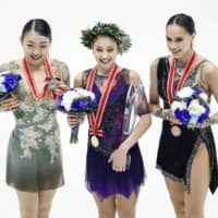 Women's champion Alena Kostornaia of Russia (center), runner-up Rika Kihira (left) and Russia's third-place finisher Alina Zagitova pose for a photo during the awards ceremony. | KYODO