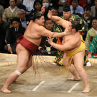 Abi (left) battles fellow komusubi Endo on Thursday at the Kyushu Grand Sumo Tournament in Fukuoka. Abi won the bout. | NIKKAN SPORTS