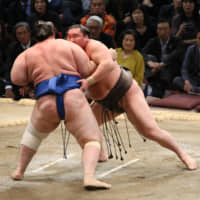 Hakuho retains top spot with win