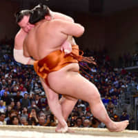 Yokozuna Hakuho hooks his right leg to sekiwake Mitakeumi's left leg to force him down en route to clinching his 43rd Emperor's Cup on the 14th day of the Kyushu Basho on Saturday at Fukuoka Kokusai Center. | NIKKAN SPORTS