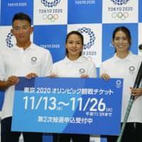 Hockey players Maho Segawa (center) and Maki Naito (right), joined by beach volleyball player Takumi Takahashi, pose at a news conference promoting the second Olympic ticket lottery for residents of Japan on Wednesday in Tokyo. | KYODO