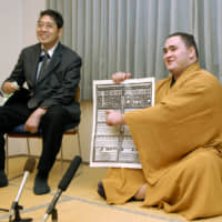 Wakanoho (right) points out his name on the banzuke ranking for the 2007 Kyushu Basho, after winning promotion to the makuuchi division, on Oct. 29, 2007, in Kitakyushu. | KYODO