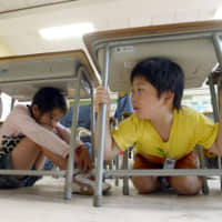 Elementary school students during an earthquake drill in Sendai. Children put on bsaizukin (disaster protection hoods) designed to guard against falling objects during and after natural disasters. | KYODO