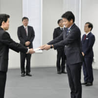 An official from the Tokyo Metropolitan Government (front, right) submits an application for a local 5G license at the Kanto Bureau of Telecommunications on Tuesday. | KYODO