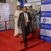 Mukesh Ambani, chairman and managing director of Reliance Industries Ltd., and his wife, Nita Ambani, arrive for the company's annual general meeting in Mumbai in August. | BLOOMBERG