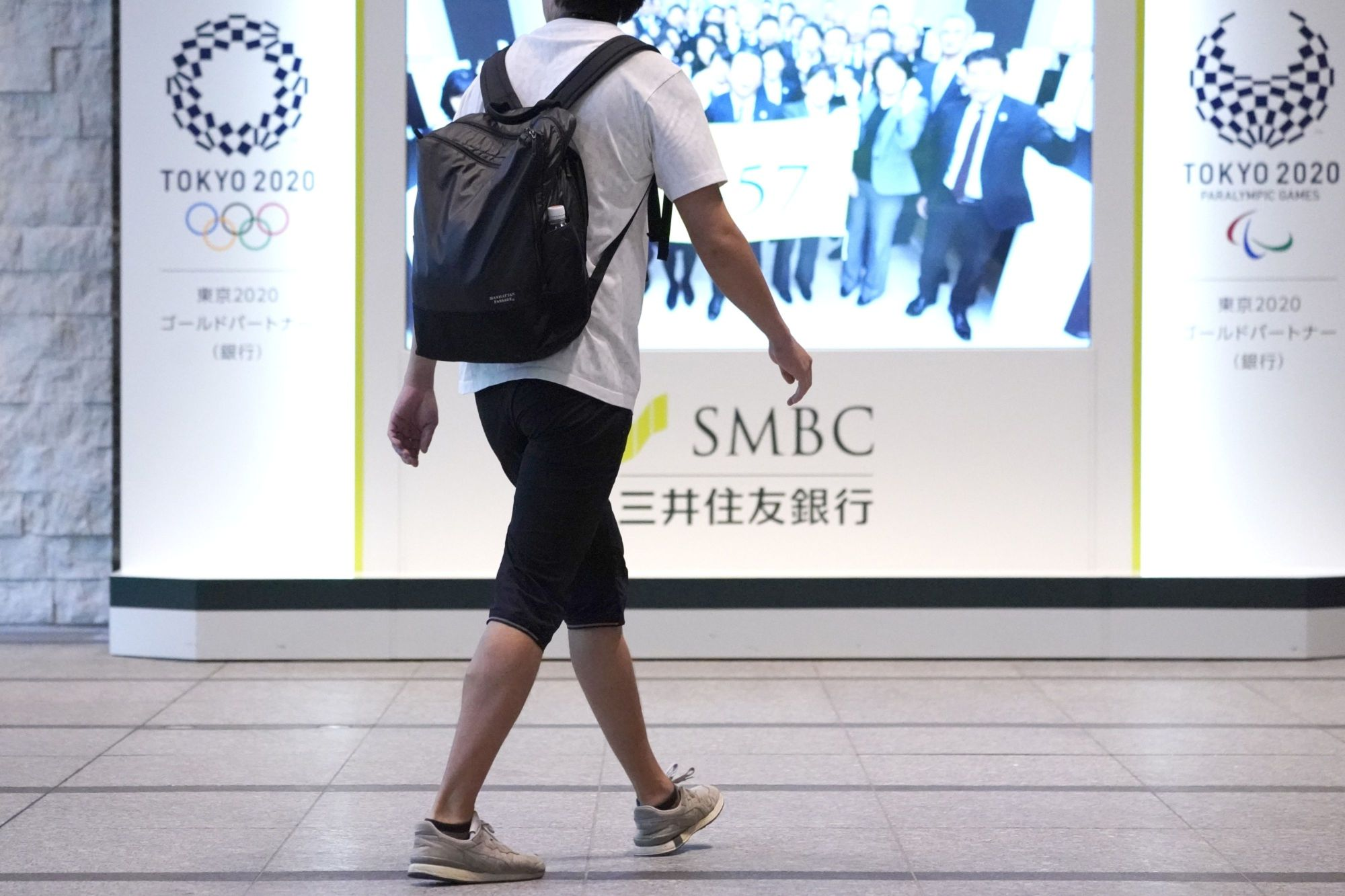 A Sumitomo Mitsui Banking Corp. employee walks towards the company's head office in Tokyo on Monday. | BLOOMBERG