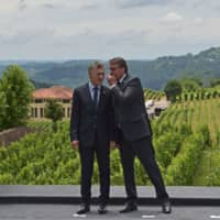 Brazilian President Jair Bolsonaro speaks with his Argentinian counterpart, Mauricio Macri, during the family picture of the 55th Mercosur summit in Bento Goncalves, Rio Grande do Sul, Brazil, on Thursday. | AFP-JIJJI