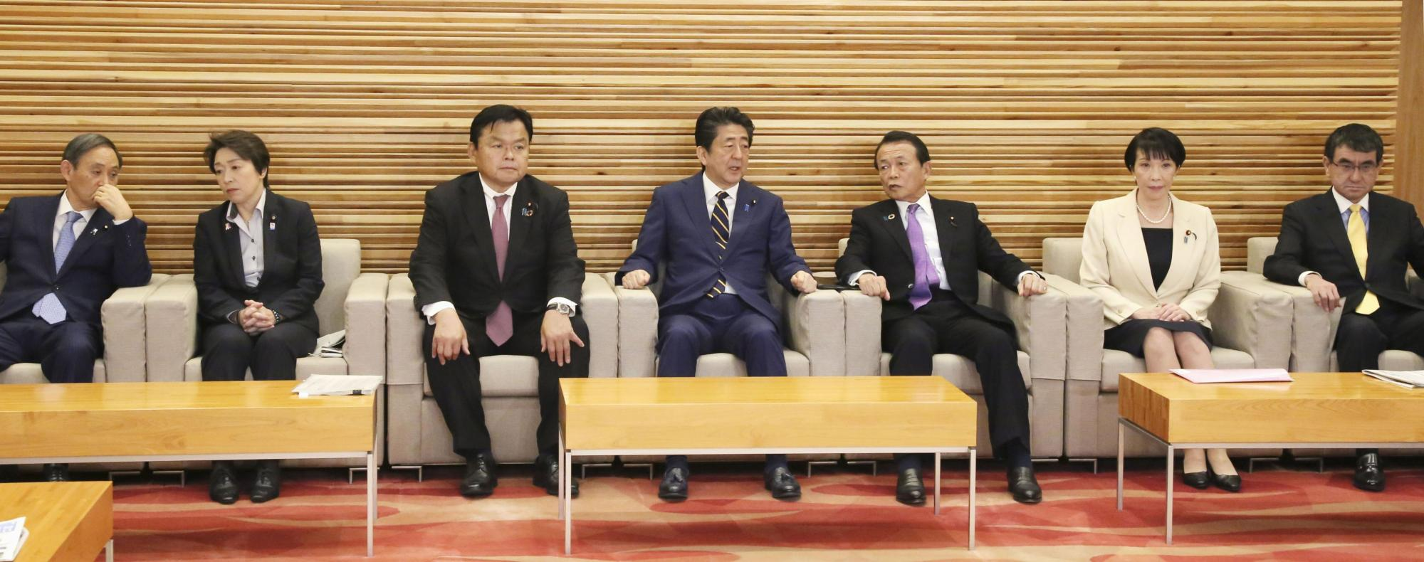 Members of Prime Minister Shinzo Abe's Cabinet attend a meeting Friday morning to adopt a record ¥102.66 trillion general account budget for the next fiscal year. | KYODO