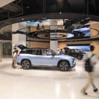 Shoppers look at a NIO ES8 sports utility vehicle at the NIO House in Shanghai Tower. | BLOOMBERG