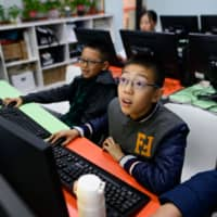 Pupils attend a class at a children's computer coding training center in Beijing on Nov. 8. China has been making huge investments in robotics and artificial intelligence, with the government issuing in 2017 an AI development plan that suggested programming courses be taught in both primary and secondary schools. | AFP-JIJI