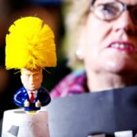A protester holds a toilet brush mocking Donald Trump as she attends a demonstration during the U.S. president's visit for a NATO summit in London Tuesday. | REUTERS