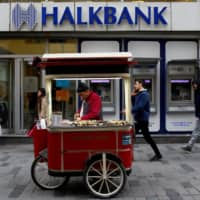 A street vendor sells roasted chestnuts in front of a branch of Halkbank in central Istanbul last year. | REUTERS