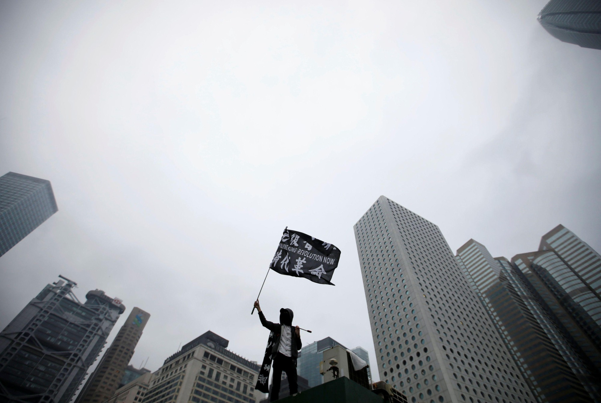 An anti-government protester waves a flag during a rally at Edinburgh Place in Hong Kong Sunday. | REUTERS