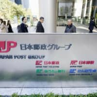 The logos of Japan Post group companies decorate the building that houses them on Friday. | KYODO