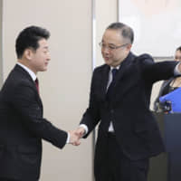 Yoichi Iida (right), head of the Trade Control Department in the Ministry of Economy, Trade and Industry, welcomes his South Korean counterpart, Lee Ho-hyeon, for talks in Tokyo on Monday. | POOL / VIA KYODO