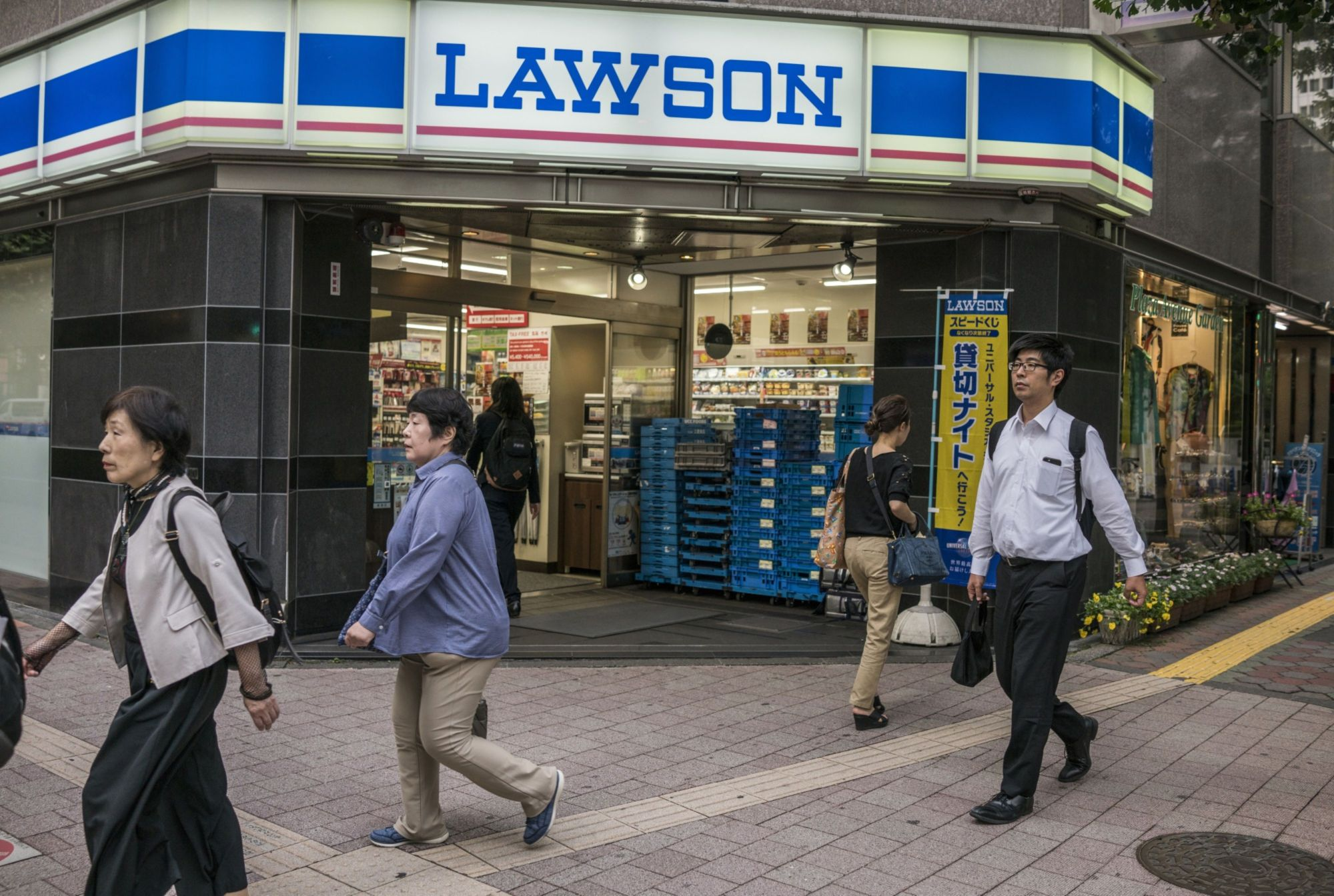 KDDI Corp. and Lawson Inc. will tie up on smartphone payments and point programs. | BLOOMBERG